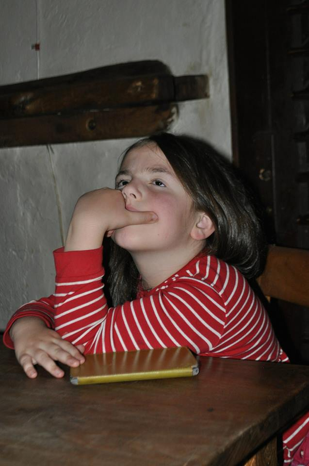 Sophia, age 8, raptly listens during Grandpa's reading in the crypt.