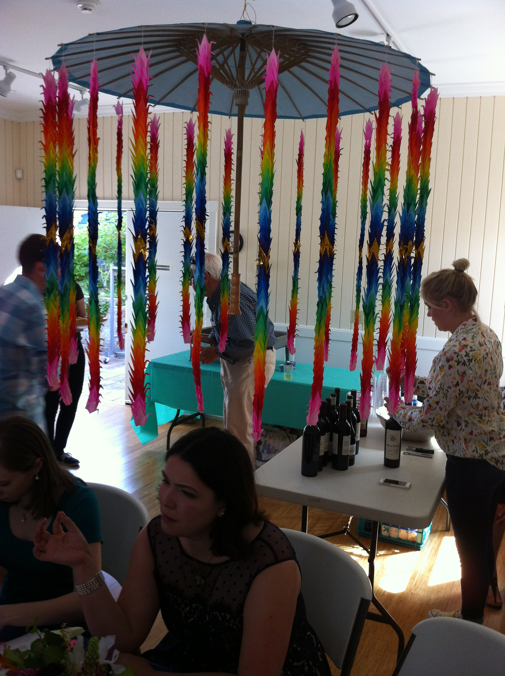 My niece sitting beneath the umbrella adorned with 1,000 paper cranes at her wedding rehearsal dinner.